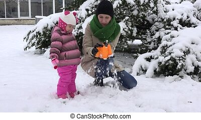 Playful mother with excited daughter girl build snow castle and destroy it
