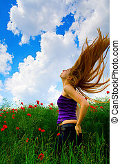 Young woman in poppy field with hair in the air