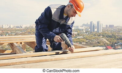 house-builder on the roof - Worker on a roof with electric...