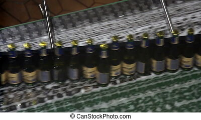 Beer bottles on conveyor of water bottling machine