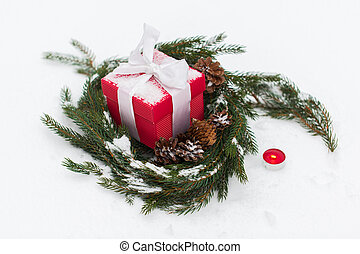 christmas gift and fir wreath with cones on snow -...