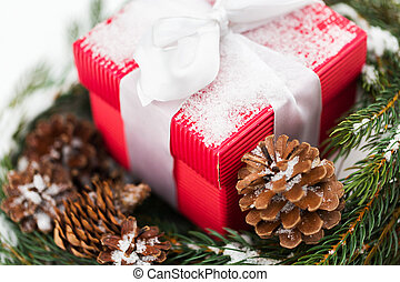 close up of christmas gift and fir wreath on snow -...