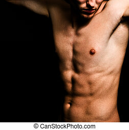 Artistic image of muscular sexy man body over black