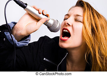 Female rock singer with microphone in hand - Portrait of...