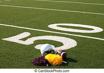 American Football Equipment and Pom Poms on Field - American...