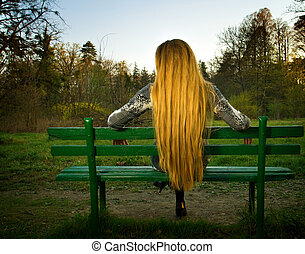 Back of woman sitting alone on park bench