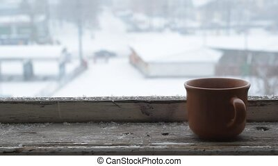 Snow falling on a cup on old wooden window sill