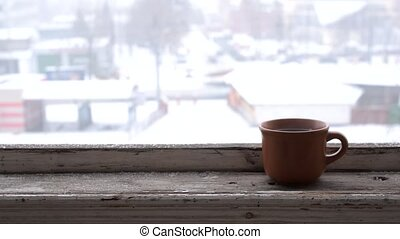 Time lapse of city road in winter with cup on window sill
