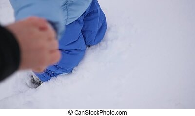 the child is go in deep snow, holding hands with mother. Closeup