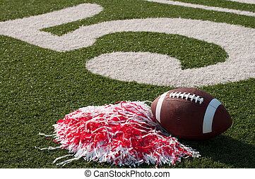 American Football and Pom Poms on Field - American football...