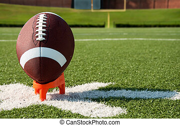 American Football Kickoff - American football on tee on...