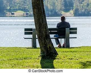 old man sitting alone on park bench. - on a park bench at a...