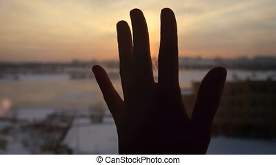Women hand touches the sun by the window on sunset city background.