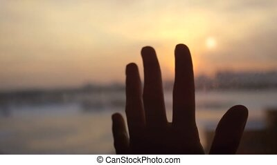Women hand touches the sun by the window on sunset city background with lens flare effects.