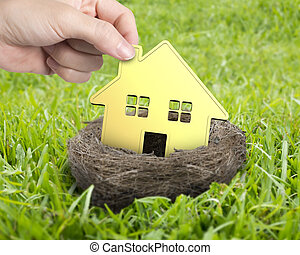 Woman hand holding golden house in nest