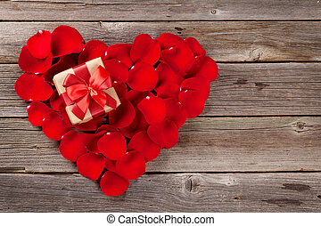 Red rose petals heart with gift box over wooden table. Top...