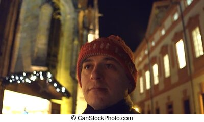 Steadicam shot a sad lonely man walking down evening street with holiday lighting decorations. 4K video
