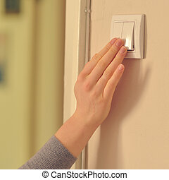 Woman hands pressing button for light on wall