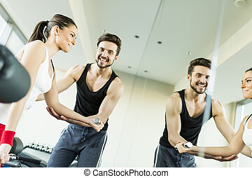 Young woman in gym exercising with her personal trainer