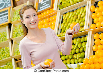 Lady in greengrocers holding an orange in each hand