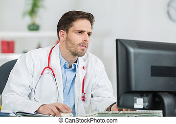 serious male doctor using computer at medical office