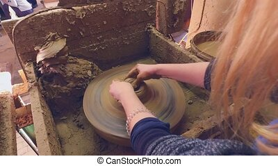 Potter's wheel. Woman's hands are trying to make Pot -...