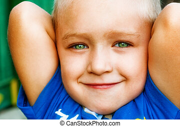 Smile of happy joyful cute kid with green eyes