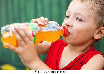 Boy drinking unhealthy bottled soda - Little boy drinking...