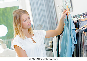 Lady in clothes shop holding top, unsure expression