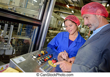 Man showing woman emergency stop button for machinery - Man...
