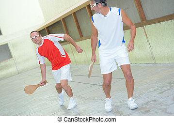 Men playing racket sport