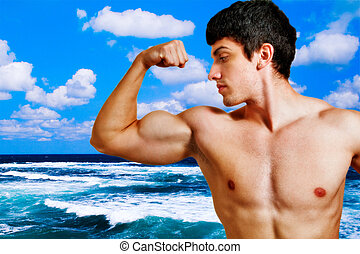 Muscular man showing his biceps on the beach - Muscular...
