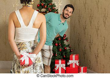 Christmas present, happy couple - Girl hiding christmas gift...