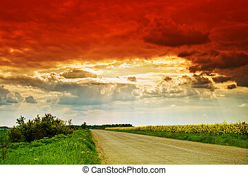 Rural road, sun rays and dramatic cloudy sky