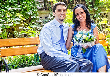 Happy married couple sitting on bench
