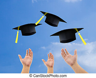 Students throwing graduation hats in the air celebrating on...