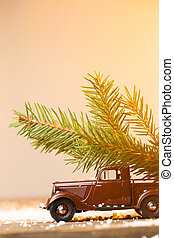 Toy car driven branch fir on wooden table with snow