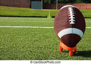 Closeup of American Football on Tee on Field - Closeup of...