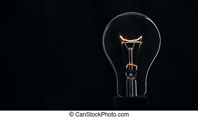 Light bulb on black background. - Light bulb on black...