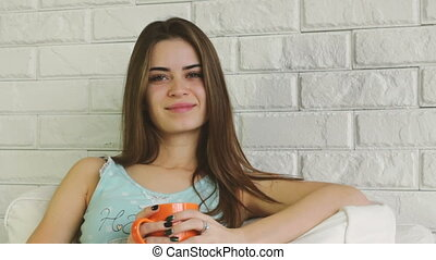 Portrait of beautiful young woman with cup of coffee or tea...