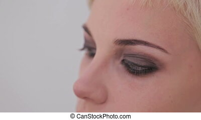Professional make-up artist combing eyebrows of client in...