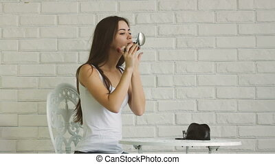 Young adult woman doing makeup by herself at home with...