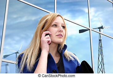 Blonde business lady with cell phone on office building...