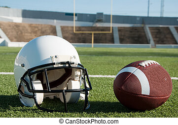 American Football and Helmet on Field - American football...