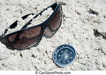 Sunglasses and compass in the sand