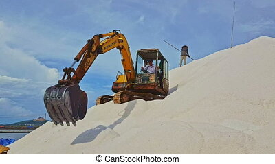 Excavator Stands on Salt Heap Pours Salt Upward with Scoop