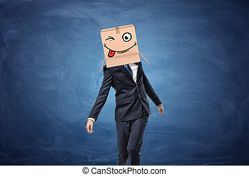 Businessman wearing cardboard box with drawn winking face on...