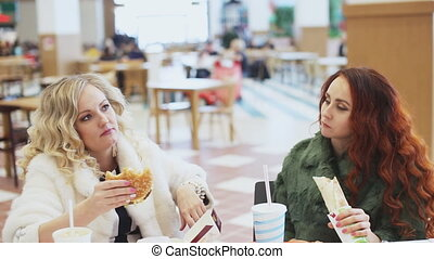 two woman eating junk food - Two girl eating fast food