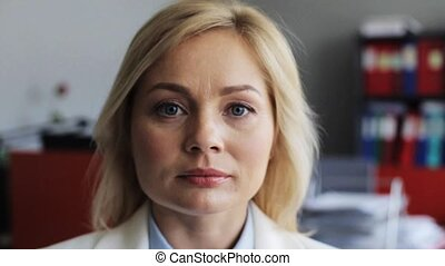 face of happy smiling middle aged woman at office -...