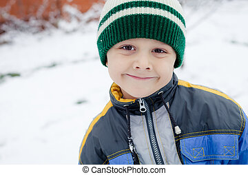 Happy little boy playing on winter snow day. Concept of...